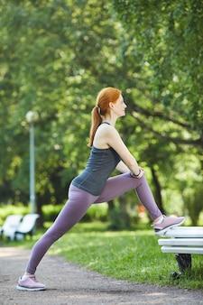 Vista lateral de uma ruiva madura magra com rabo de cavalo, apoiando o pé no banco enquanto faz exercícios de alongamento no parque da cidade