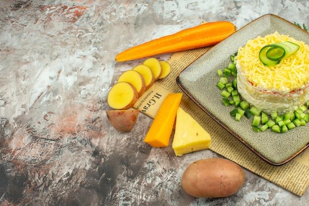 Vista lateral de uma saborosa salada servida com pepino picado em um jornal velho e dois tipos de queijo e batatas com cenoura em mesa de cores mistas