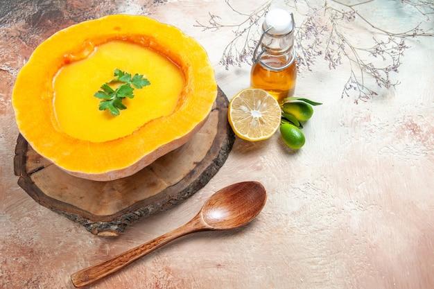 Vista lateral de uma sopa de abóbora sopa com ervas no quadro colher óleo limão ramos