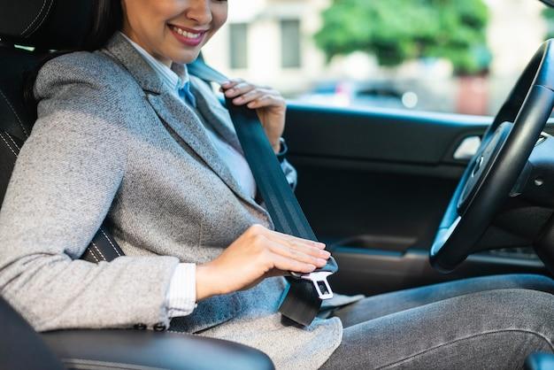 Vista lateral de uma sorridente empresária colocando o cinto de segurança no carro