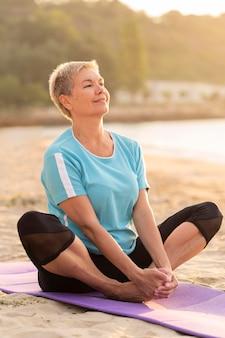 Vista lateral de uma sorridente mulher sênior fazendo ioga na praia