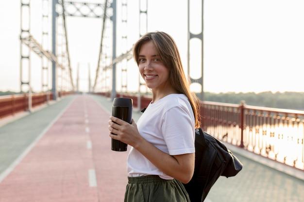 Vista lateral de uma sorridente mulher viajando segurando uma garrafa térmica na ponte