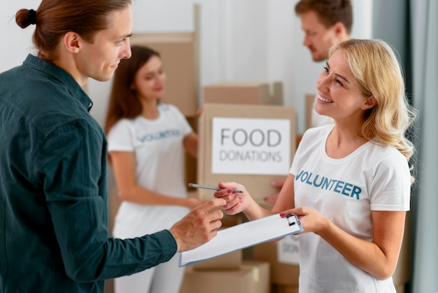 Vista lateral de uma sorridente voluntária ajudando uma pessoa necessitada