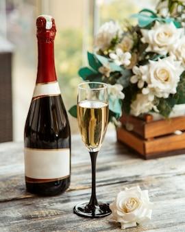 Vista lateral de uma taça de champanhe com uma garrafa e rosas brancas