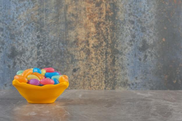 Vista lateral de uma tigela de laranja cheia de doces de balas de geleia.