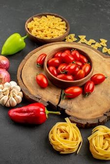 Vista lateral de uma tigela de longe na tigela de tomate na tábua de cortar macarrão e cebola, pimentão e alho na mesa