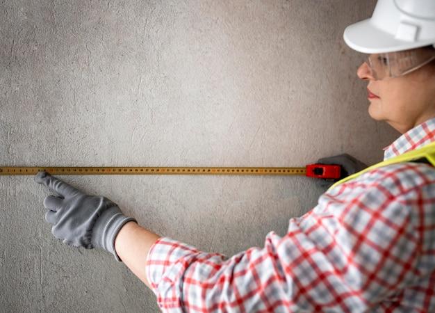 Vista lateral de uma trabalhadora da construção civil com capacete e fita métrica