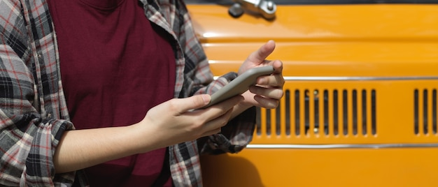 Vista lateral de uma trabalhadora enviando mensagens de texto no smartphone em frente ao carro dela
