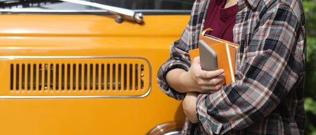 Vista lateral de uma trabalhadora segurando notebooks e smartphone em frente ao carro
