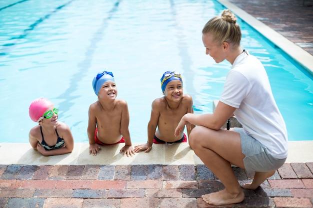 Vista lateral de uma treinadora de natação ensinando alunos ao lado da piscina