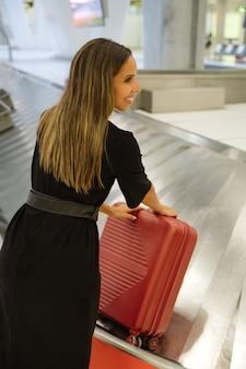 Vista lateral de uma viajante levando mala da esteira na área de retirada de bagagem do aeroporto