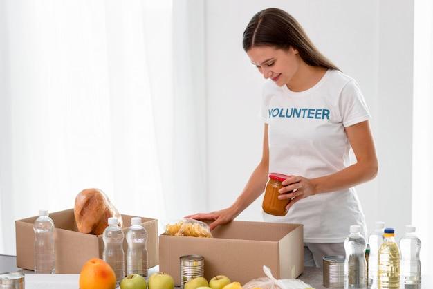 Vista lateral de uma voluntária embalando alimentos em caixas para doação