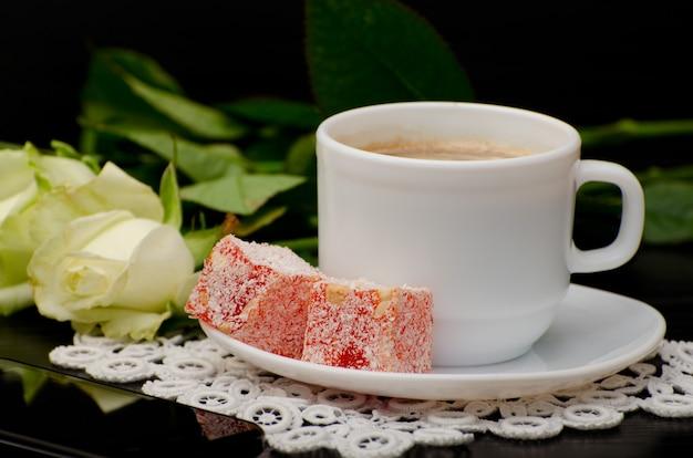 Vista lateral de uma xícara de café com close-up de leite, doces orientais. rosas brancas em um preto