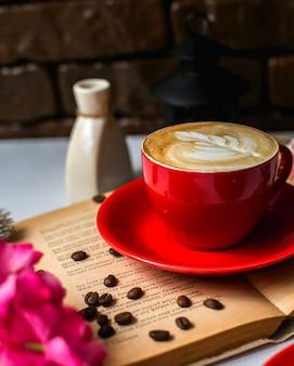 Vista lateral de uma xícara de café com leite e grãos de café na mesa