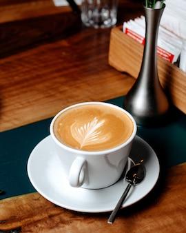 Vista lateral de uma xícara de café com leite na mesa de madeira