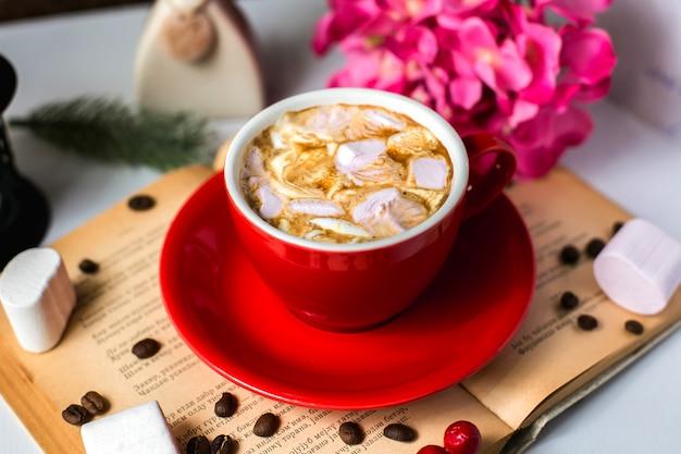 Vista lateral de uma xícara de café com marshmallows e grãos de café na mesa