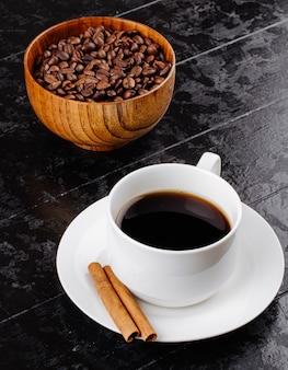 Vista lateral de uma xícara de café com paus de canela e uma tigela de madeira com grãos de café