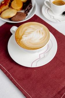 Vista lateral de uma xícara de café e doces