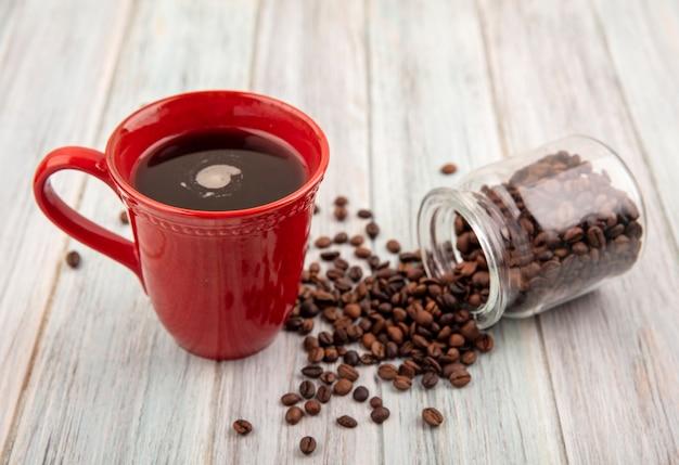 Vista lateral de uma xícara de café e grãos de café derramando da jarra de vidro no fundo de madeira
