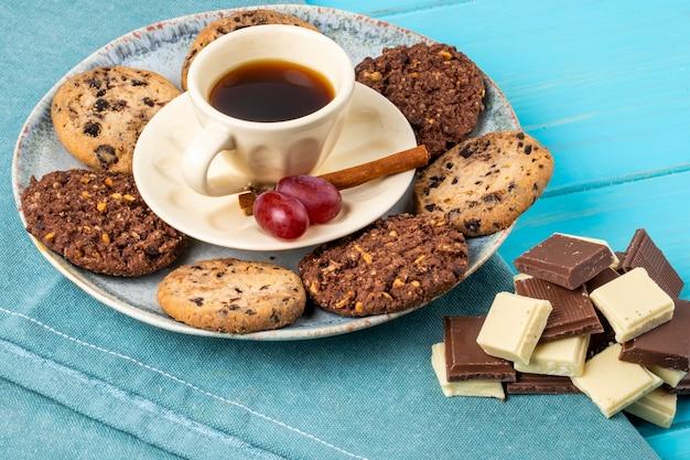 Vista lateral de uma xícara de café servido com biscoitos de aveia e chocolate no fundo azul