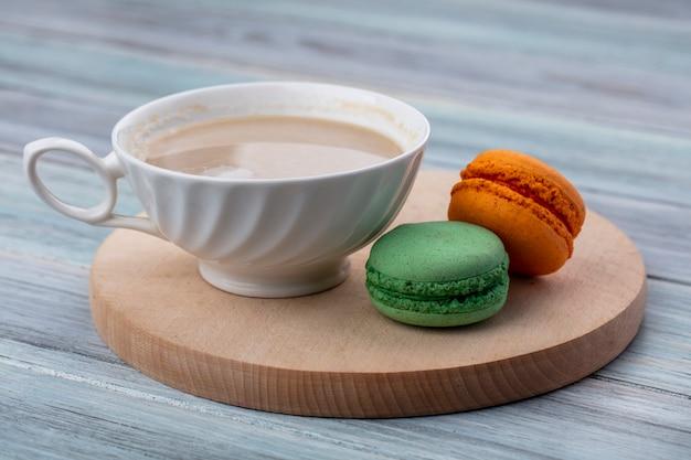 Vista lateral de uma xícara de cappuccino com macarons coloridos em um suporte de madeira em uma superfície cinza