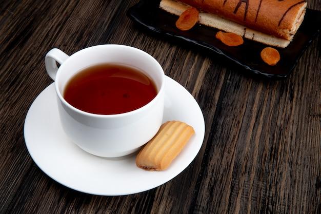 Vista lateral de uma xícara de chá com biscoito e rolo de bolo em uma bandeja na superfície de madeira rústica