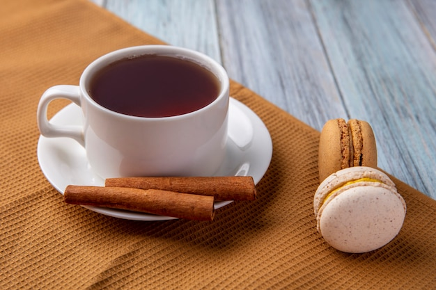 Vista lateral de uma xícara de chá com canela e macarons em uma toalha marrom sobre uma superfície cinza