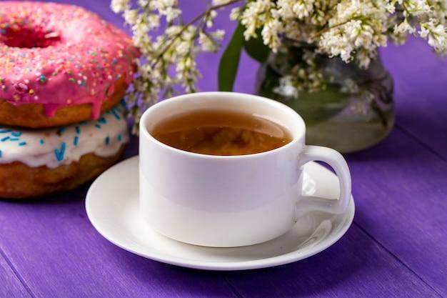 Vista lateral de uma xícara de chá com donuts e flores em uma superfície roxa brilhante