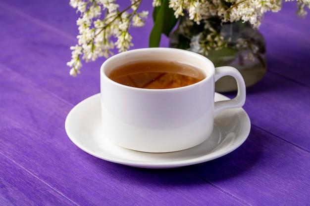 Vista lateral de uma xícara de chá com flores em uma superfície roxa brilhante