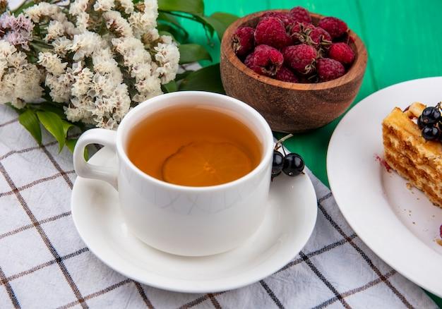 Vista lateral de uma xícara de chá com framboesas e flores em uma toalha xadrez