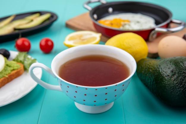Vista lateral de uma xícara de chá com limão ovo frito em uma panela sobre uma tábua de madeira da cozinha com ingredientes na superfície azul