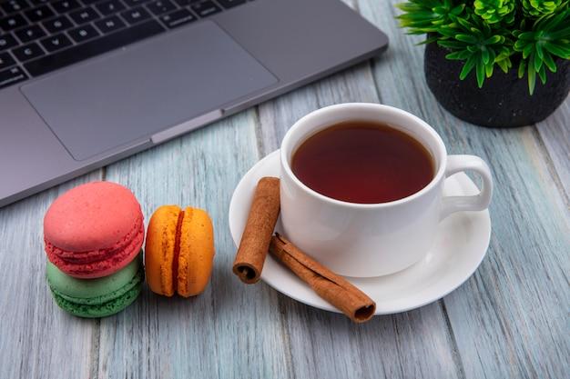 Vista lateral de uma xícara de chá com macarons cor de canela e um laptop em uma superfície cinza