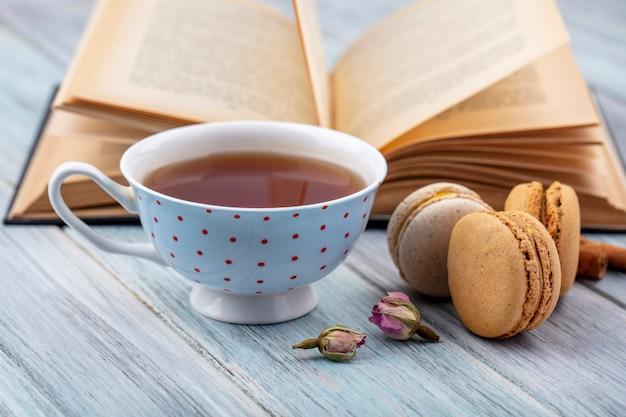 Vista lateral de uma xícara de chá com macarons e um livro aberto em uma superfície cinza
