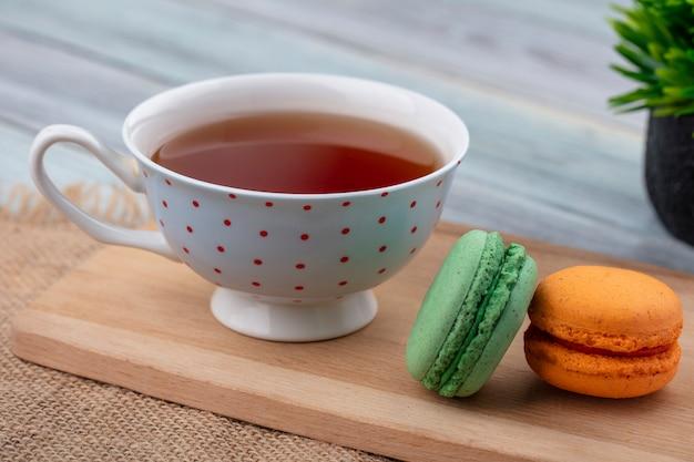 Vista lateral de uma xícara de chá com macarons em uma tábua