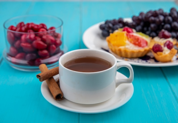 Vista lateral de uma xícara de chá com paus de canela com bagas de cornel em uma tigela de vidro sobre um fundo azul de madeira