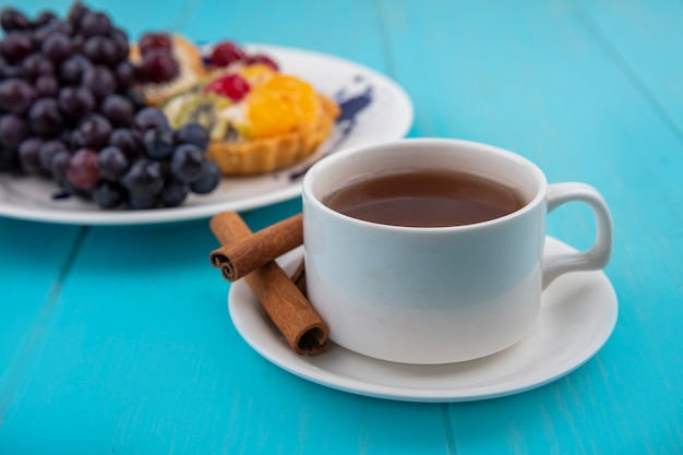 Vista lateral de uma xícara de chá com paus de canela em um fundo azul de madeira