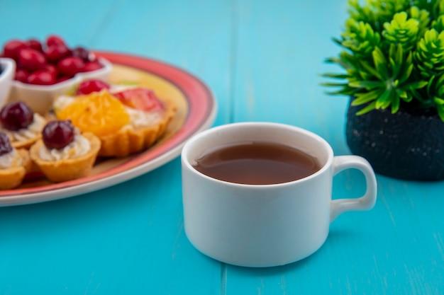 Vista lateral de uma xícara de chá com um prato de tortas em um fundo azul de madeira