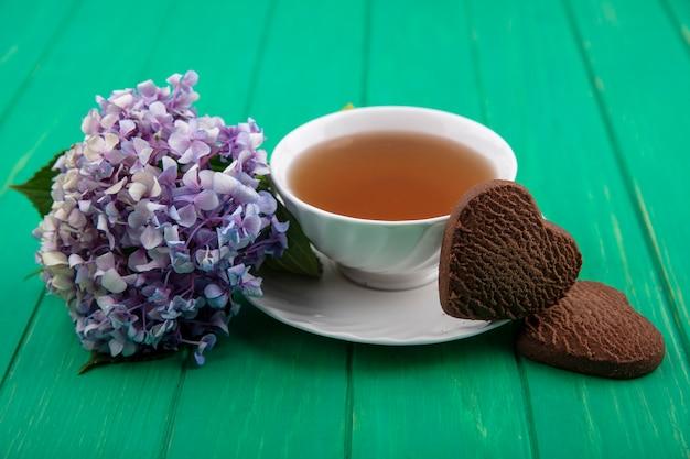 Vista lateral de uma xícara de chá e biscoitos em forma de coração com flores sobre fundo verde