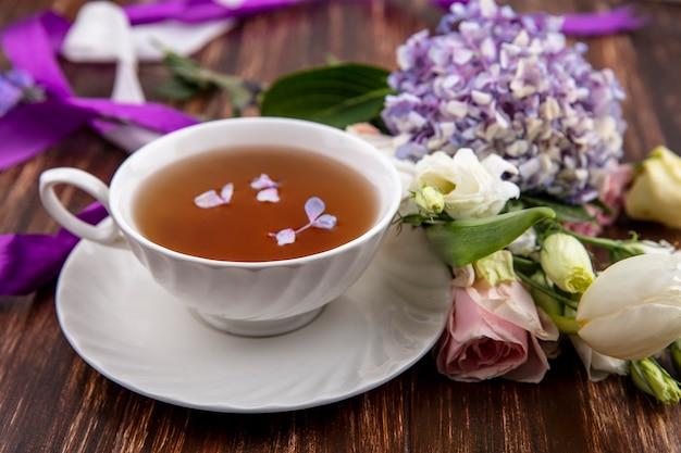 Vista lateral de uma xícara de chá no pires e flores com fitas no fundo de madeira