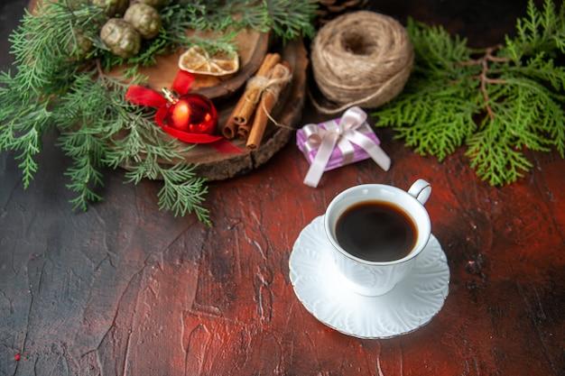 Vista lateral de uma xícara de chá preto com galhos de pinheiro e um caderno espiral fechado com uma bola de corda de canela e limão no fundo escuro