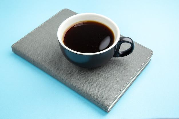 Vista lateral de uma xícara de chá preto em um caderno cinza na superfície azul