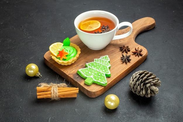 Vista lateral de uma xícara de cone de conífera de acessórios de ano novo de chá preto e limão com canela em fundo preto