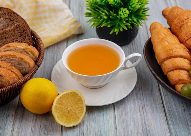 Vista lateral de uma xícara de hot toddy no pires com fatias de pão crocante de centeio na cesta e croissants em uma tigela com metade do limão cortado e planta no fundo de madeira