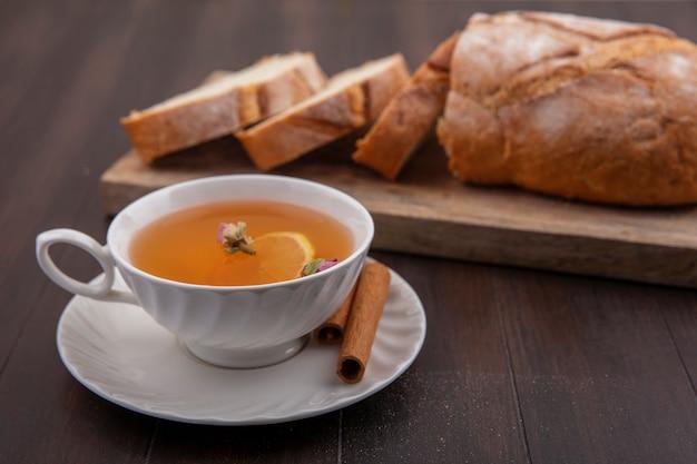 Vista lateral de uma xícara de toddy quente com flor de limão dentro e canela no pires com corte e fatias de pão crocante na tábua com fundo de madeira