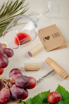 Vista lateral de uva fresca, pequeno cartão postal, parafuso de garrafa com rolhas de vinho e um copo de vinho deitado na mesa branca