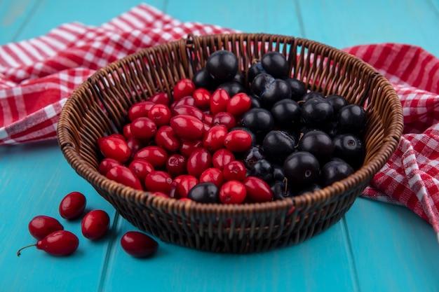 Vista lateral de uva preta em um balde com cerejas vermelhas em um balde em um pano xadrez vermelho sobre um fundo azul de madeira com espaço de cópia
