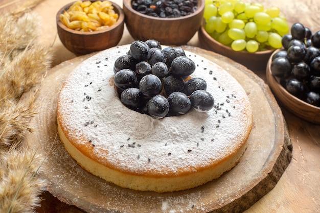 Vista lateral de uvas em close-up, um bolo com tigelas de uvas passas e espiguetas de uvas