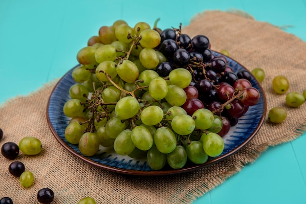 Vista lateral de uvas em prato com bagas de uva em pano de saco no fundo azul