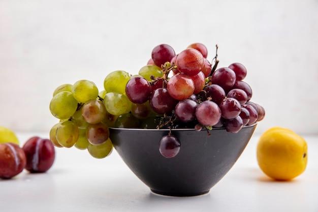 Vista lateral de uvas em uma tigela com pluots e nectacot em fundo branco