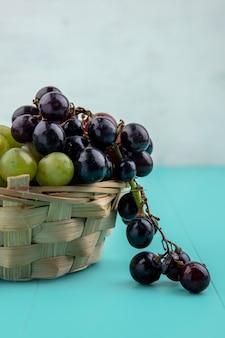 Vista lateral de uvas pretas e brancas em uma cesta na superfície azul e fundo branco